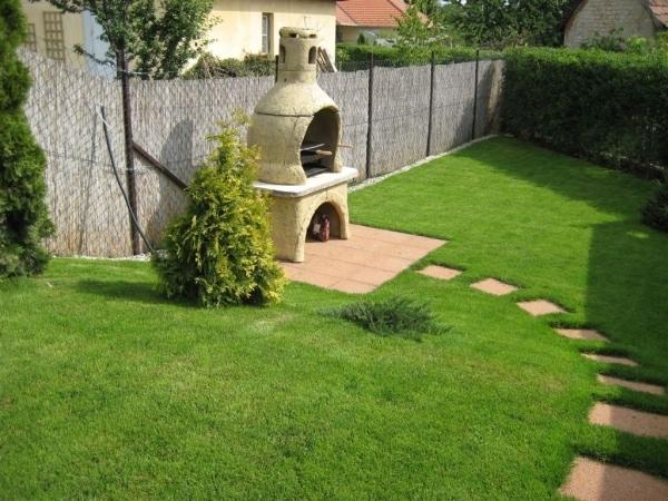 A kerti grill köré térburkolat került, a kerti sütő környezetébe pedig aranyciprus és kúszó boróka - csupa örökzöld, hogy a kerti zöldhulladék minél kevesebb legyen.